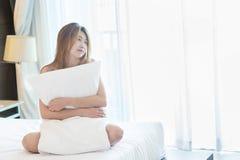 Mujer hermosa de Asia que presenta en toalla en cama fotografía de archivo