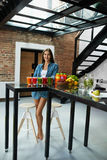 Mujer hermosa de consumición sana con Juice Smoothie Indoors fresco Imagen de archivo libre de regalías