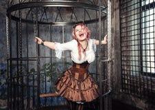 Mujer hermosa de griterío del steampunk en la jaula Fotos de archivo