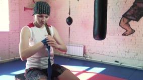 Mujer hermosa de Kickboxing que pone en los abrigos de perforación en el cuerpo apto 4k de la fuerza feroz del estudio de la apti metrajes