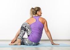 Mujer hermosa de la aptitud que hace ejercicios de la yoga en un fondo ligero imágenes de archivo libres de regalías