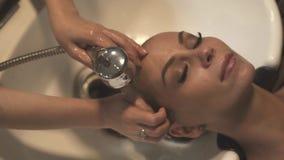 Mujer hermosa de la cara mientras que lava el pelo con champú en salón de la peluquería Mujer joven que consigue la cabeza que se metrajes