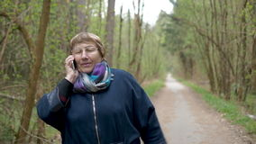 Mujer hermosa de la edad, hablando en el teléfono, sonrisa, feliz con las buenas noticias Para una caminata en el parque almacen de metraje de vídeo