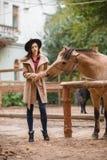 Mujer hermosa de la elegancia que frota ligeramente un caballo al aire libre Imagenes de archivo