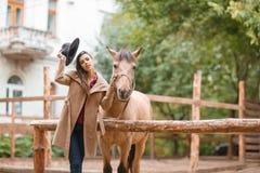 Mujer hermosa de la elegancia que presenta con el caballo al aire libre Foto de archivo