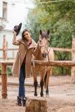 Mujer hermosa de la elegancia que presenta con el caballo al aire libre Fotografía de archivo