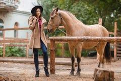 Mujer hermosa de la elegancia que presenta con el caballo al aire libre Fotos de archivo