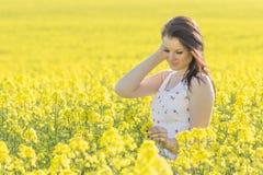 Mujer hermosa de la juventud con la flor en el prado del verano que mira abajo Foto de archivo