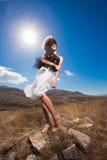 Mujer hermosa de la manera que presenta en las montañas Imagen de archivo
