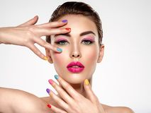 Mujer hermosa de la moda con clavos coloreados Muchacha blanca atractiva con la manicura multicolora fotografía de archivo