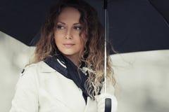 Mujer hermosa de la moda con el paraguas que camina en la calle de la ciudad Foto de archivo libre de regalías