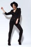 Mujer hermosa de la moda con el sombrero en traje negro Imagen de archivo