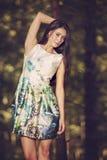 Mujer hermosa de la moda de los jóvenes en la presentación del vestido del color al aire libre en g Imágenes de archivo libres de regalías