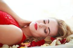 Mujer hermosa de la moda en pétalos color de rosa rojos en blanco fotografía de archivo