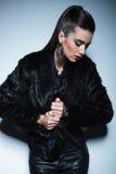 Mujer hermosa de la moda que tira de su abrigo de pieles Imagen de archivo