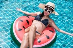 Mujer hermosa de la muchacha que se relaja en lilo de la sandía en piscina Fotos de archivo libres de regalías