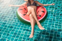 Mujer hermosa de la muchacha que se relaja en lilo de la sandía en piscina Foto de archivo libre de regalías