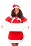 Mujer hermosa de la Navidad en el sombrero de santa con el tablero blanco en blanco Imágenes de archivo libres de regalías