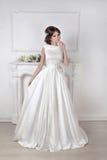 Mujer hermosa de la novia que presenta en vestido magnífico sobre wal blanco fotos de archivo