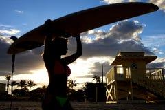 Mujer hermosa de la silueta que sostiene una tabla hawaiana fotos de archivo