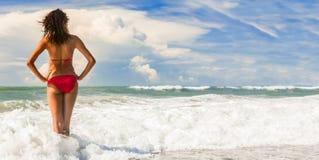 Mujer hermosa de la vista posterior en bikini rojo en la playa imagenes de archivo