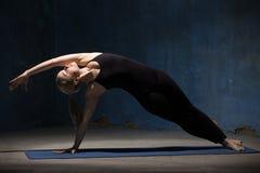 Mujer hermosa de la yoga que hace actitud lateral del tablón Imágenes de archivo libres de regalías