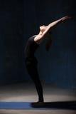 Mujer hermosa de la yoga que hace la actitud de Ardha Chakrasana Imagenes de archivo