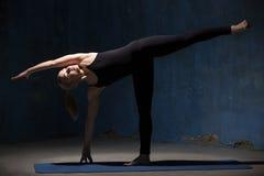 Mujer hermosa de la yoga que hace la actitud de Ardha Chandrasana Foto de archivo