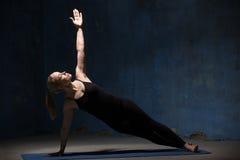 Mujer hermosa de la yoga que hace la actitud de Vasisthasana Imágenes de archivo libres de regalías