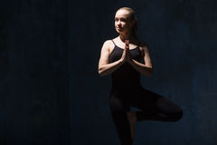 Mujer hermosa de la yoga que hace la actitud de Vrksasana Foto de archivo libre de regalías