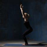 Mujer hermosa de la yoga que se coloca en actitud de la silla Fotografía de archivo