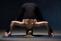 Mujer hermosa de la yoga que se coloca en actitud delantera Ancho-Legged de la curva Imagen de archivo