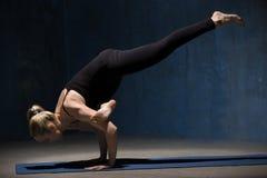 Mujer hermosa de la yoga que se coloca en la actitud de Eka Pada Galavasana Fotografía de archivo libre de regalías