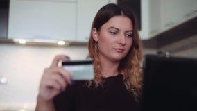 Mujer hermosa de las actividades bancarias en línea con una ayuda del ordenador móvil y de la tarjeta de crédito que tienen un bu almacen de video