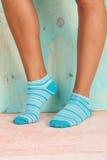 Mujer hermosa de las piernas con los calcetines que se colocan de puntillas en el piso de madera Foto de archivo
