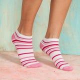 Mujer hermosa de las piernas con los calcetines que se colocan de puntillas en el piso de madera Imagen de archivo libre de regalías