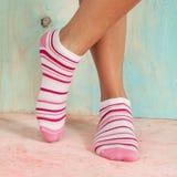 Mujer hermosa de las piernas con los calcetines que se colocan de puntillas en el piso de madera Imagen de archivo