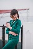 Mujer hermosa de moda joven con el café a ir a presentar en la ciudad Fotografía de archivo