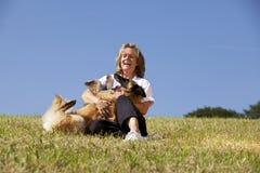 Mujer hermosa de risa que juega con su perro Foto de archivo libre de regalías