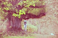 Mujer hermosa debajo del árbol de arce masivo, bosquejo fotografía de archivo