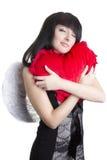 Mujer hermosa del ángel que abraza el corazón rojo Imagen de archivo