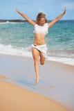 Mujer hermosa del ajuste que salta en la playa Fotografía de archivo libre de regalías