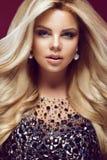 Mujer hermosa del blondie del encanto en vestido elegante con las joyas, igualando maquillaje y rizos La belleza de la cara fotos de archivo