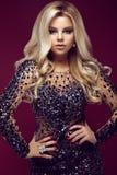 Mujer hermosa del blondie del encanto en vestido elegante con las joyas, igualando maquillaje y rizos La belleza de la cara foto de archivo libre de regalías