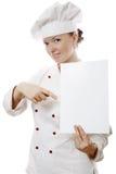 Mujer hermosa del cocinero que lleva a cabo una tarjeta de aviso Imagenes de archivo