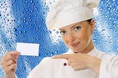 Mujer hermosa del cocinero que sostiene la tarjeta en blanco imagen de archivo libre de regalías