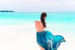 Mujer hermosa del cuerpo del bikini que se relaja en abrigo de la moda de la ropa de playa del encubrimiento que fluye en fondo d imagenes de archivo
