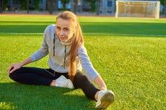 Mujer hermosa del deporte que hace estirando ejercicio de la aptitud en parque de la ciudad en la hierba verde Posturas de la yog Fotos de archivo libres de regalías