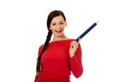 Mujer hermosa del estudiante que destaca con un lápiz grande Imagen de archivo
