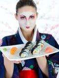 Mujer hermosa del geisha de Japón con el conjunto del sushi Imagenes de archivo